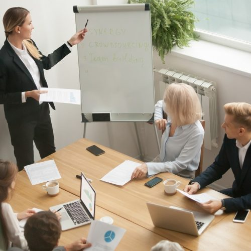 Businesswoman ceo boss in suit presenting corporate strategy pointing on flip chart at group meeting, business coach leader giving presentation explaining team goals in conference room at training